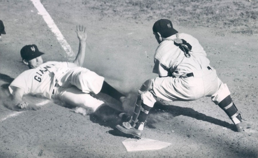 Giants shortstop Alvin Dark is safe at home plate as Yankees catcher Yogi Berra can't handle the ball
