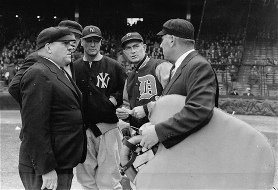 Yankee captain Lou Gehrig stuns Tigers manager Del Baker, home plate umpire Steve Basil and umpires Red Ornsby and Bill Summers as Gehrig informs them he has benched himself.