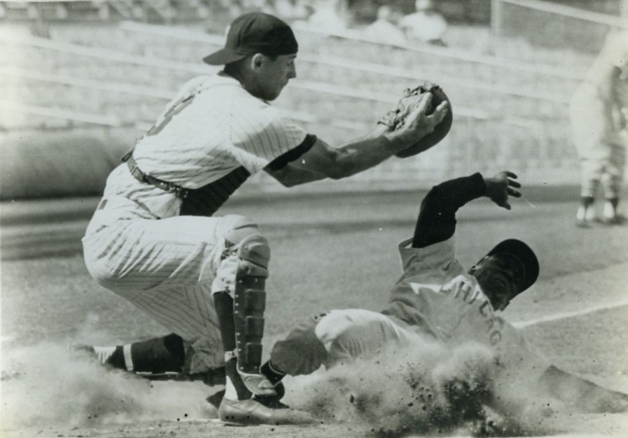 White Sox outfielder Minnie Minoso scores on a short pop fly hit by Nellie Fox. Kansas City Athletics catcher Haywood Sullivan tries to apply the tag, The White Sox won this first game of a doubleheader 5-3. (Sept 20, 1961) photo: UPI