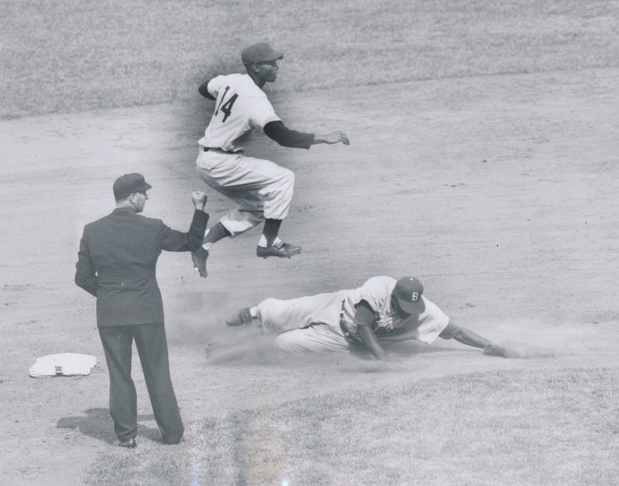 Jackie Robinson forced out at second base as Ernie Banks leaps over him May 11, 1955 photo: UPI