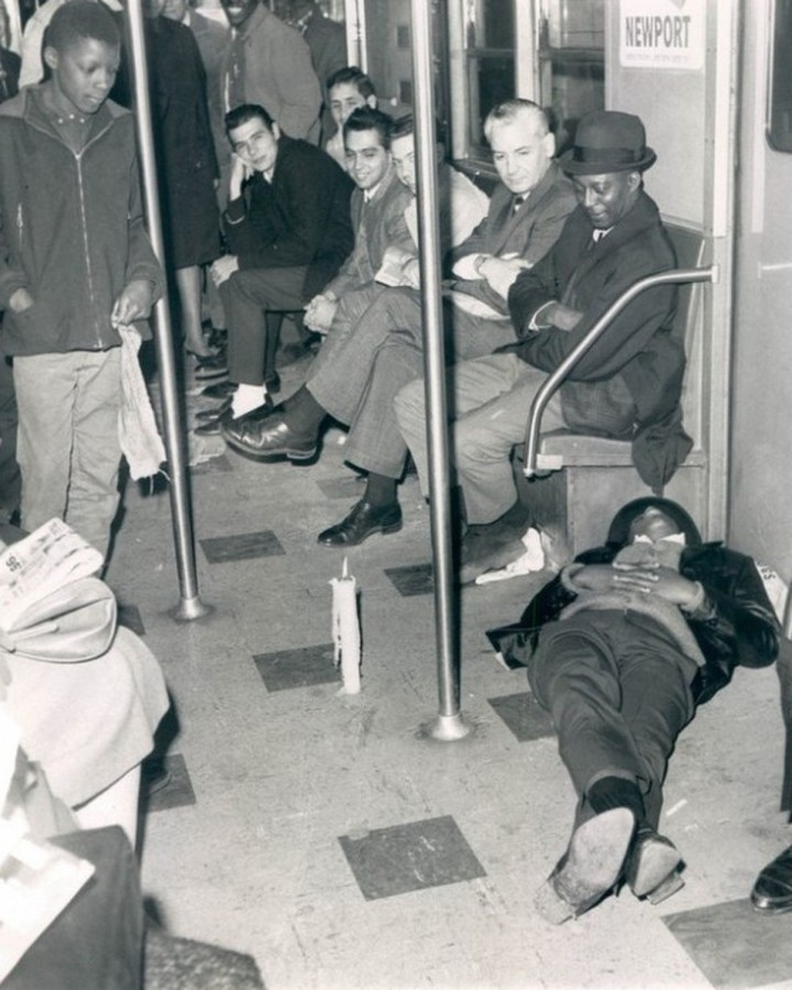 Blackout: Using a candle for a light passengers look at another passenger sleeping on the floor of a stalled subway train during power failure. November 10, 1965 (AP Wirephoto)