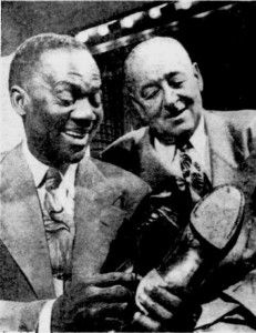 Bill Robinson, with manager Marty Forkins, holds tap shoes he has used for the last 25 years. Dec 31, 1947 Milwaukee Sentinel