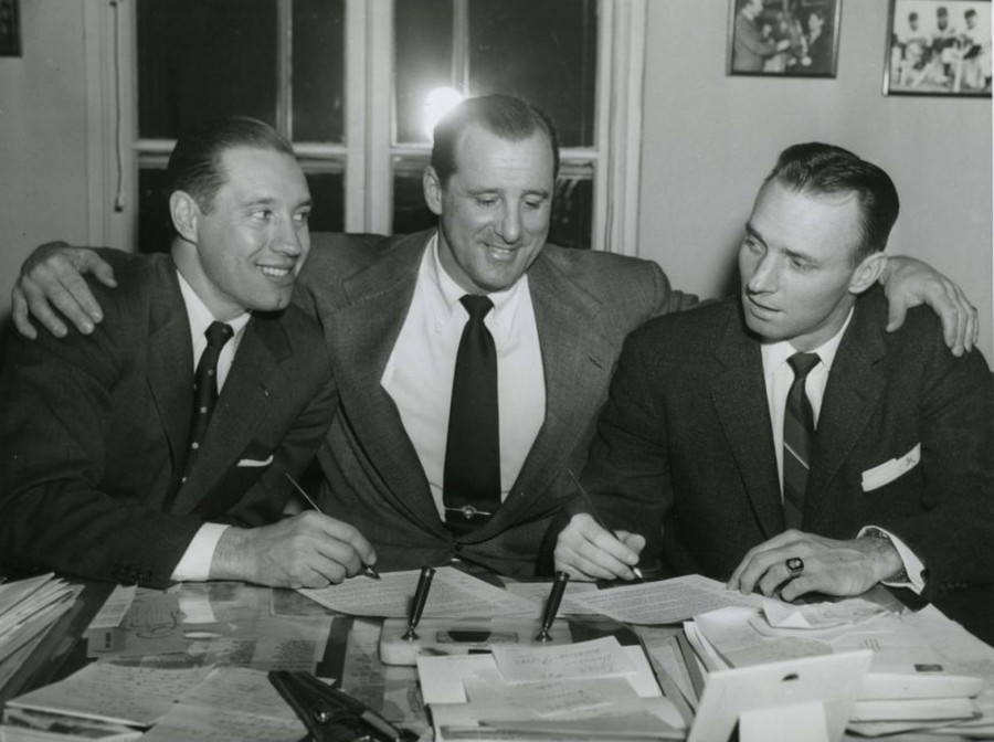 Indians pitcher Bob Feller (l) and catcher Jim Hegan (r) sit between GM Hank Greenberg as they sign their 1956 contracts - February 9, 1956