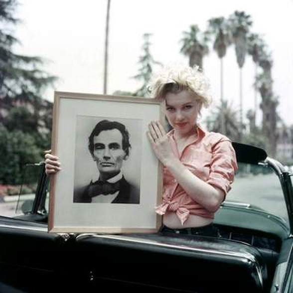 Marilyn Monroe in Cadillac holding a portrait of Abraham Lincoln. photograph: Milton Greene
