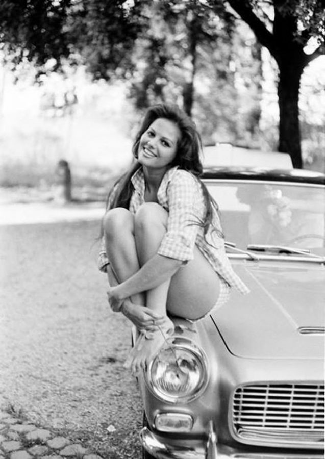 Claudia Cardinale sits on a car