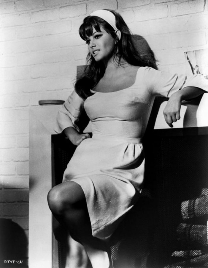 Claudia Cardinale standing near fireplace
