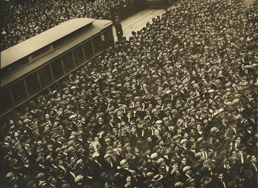 1911 World Series Game 6. A multitude of humanity stands outside the New York Herald Building watching the Play-O-Graph and the cameraman. Double click the photo and see many men looking up and smiling at the camera.